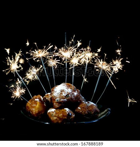 a pile with oliebollen with fireworks on a plate on a white background - stock photo