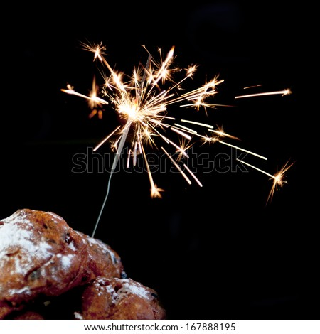 a pile with oliebollen with fireworks on a white background - stock photo