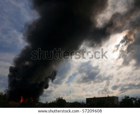 A pillar of black smoke above the burning building.
