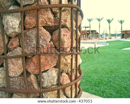 A pillar of rocks, wrapped in rebar rests in the foregound. A path of green grass leads to palm trees and a picnic area - stock photo