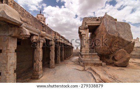 A pillared corridor runs in front of a huge idol of lord Ganesha at the ancient temple at Lepakshi, Andhra Pradesh - stock photo