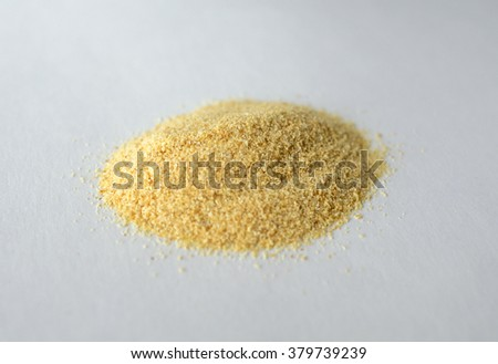 A pinch of small granulated garlic on white background  - stock photo
