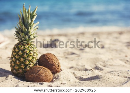 a pineapple and two coconuts on the beach sand - stock photo