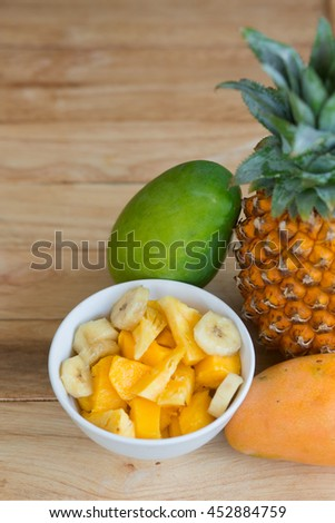 A pineapple, yellow and green mangoes and a bowl of exotic fruit salad