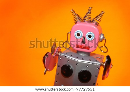 a pink and silver toy maid robot with an orange background - stock photo