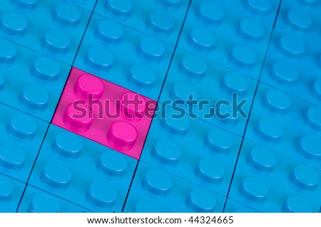 A pink building block, fitted in a field of blue ones - stock photo