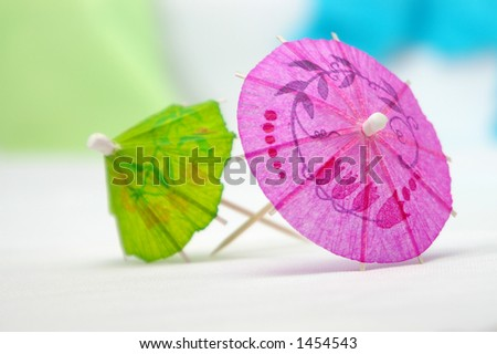 A pink cocktail umbrella, along with a green umbrella in the background. - stock photo