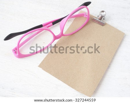 a pink glasses with a notepaper  - stock photo
