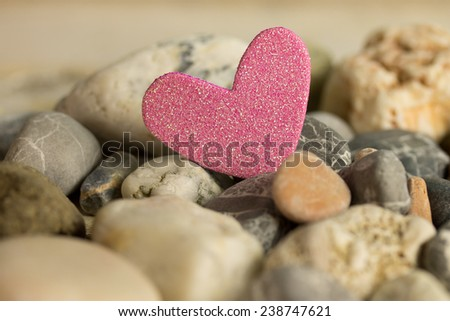 a pink heart between stones  - stock photo