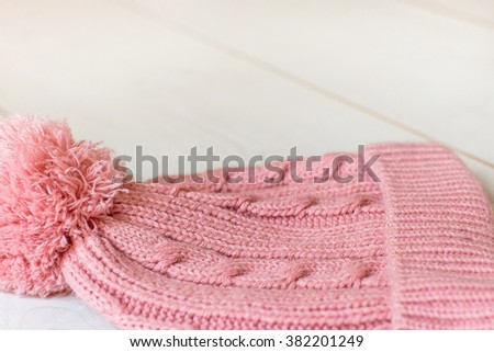 A pink knitted hat on a white background