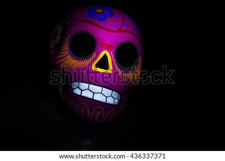 A pink mexican skull on a dark background. - stock photo