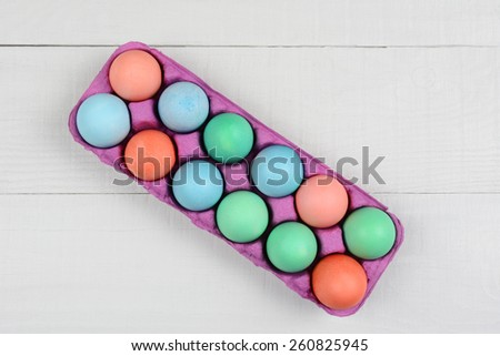 A pink one dozen carton of dyed Easter Eggs on a white wood kitchen table. Horizontal format with the carton at an angle. Overhead view. - stock photo