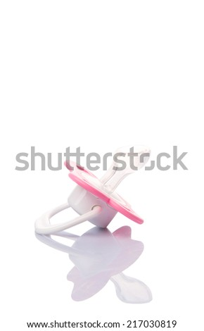 A pink pacifier over white background