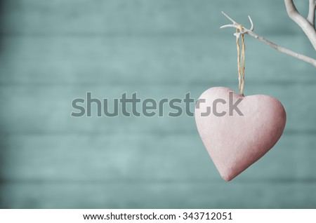 A pink painted heart, hanging from branch of white artificial tree, with faded turquoise wood plank soft focus background. Pastel hues. - stock photo