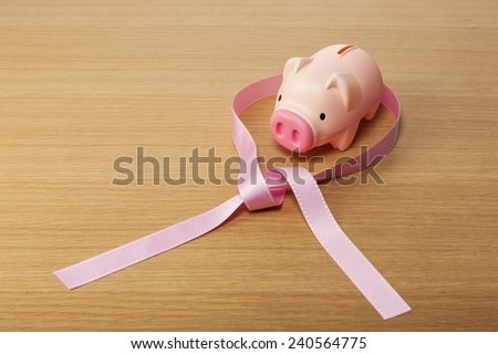 A pink pig coin bank(money box) with pink ribbon on the wooden office desk(table). - stock photo