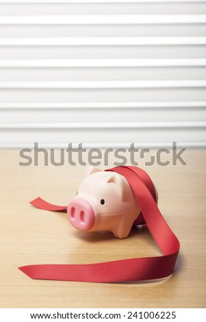 A pink pig coin bank(money box) with red ribbon on the wood office desk(table) behind white blind.  - stock photo