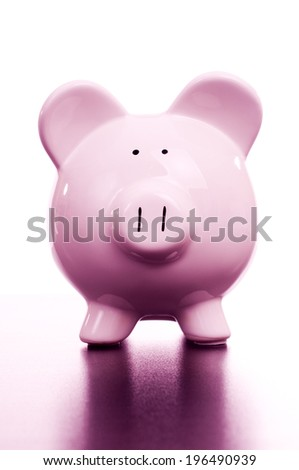 A pink pig shaped piggy bank reflected on a surface.