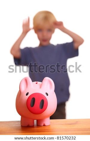 A pink piggy bank on front of a young boy - stock photo