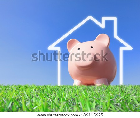 A pink piggy bank with new home house imagination vision with blue sky - stock photo