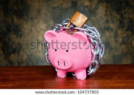 A pink piggybank chained up and locked. Image can be used for financial protection inferences or other investment messages. - stock photo
