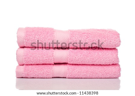 A pink towels stacked reflected on white background - stock photo