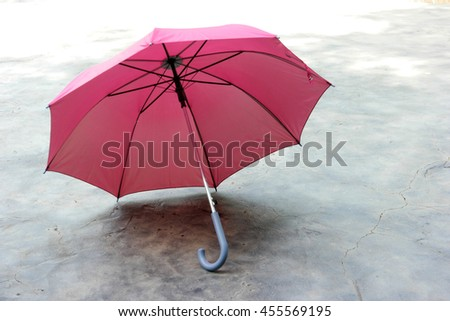 a pink umbrella with grey handle placing on the concrete floor. Focusing to the umbrella handle. - stock photo