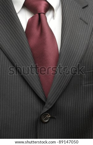 A pinstriped charcoal grey wool men's business suit with a silk tie and plain shirt. - stock photo
