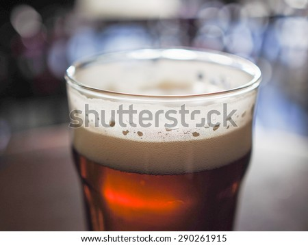 A pint of beer in a pub, focus on beer and blurred background bokeh - stock photo