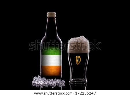 A Pint of Dark Beer and a Beer Bottle on a Black Background. Irish Beer Concept  - stock photo
