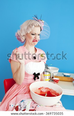 A pinup girl tastes her cake batter and finds out it tastes horrible. - stock photo