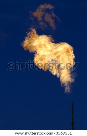A pipe used to burn-off natural gas from a North Texas neighborhood well. - stock photo