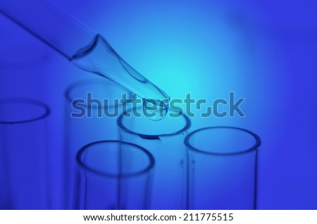 A pipette dropping sample into a test tube