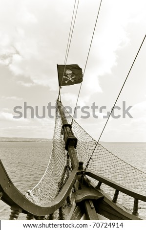 A pirate flag on the bow of the ship - stock photo