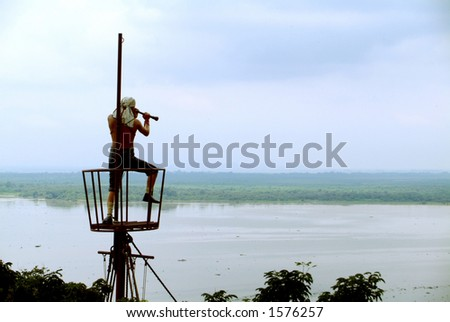 A pirate looks out on to the water from a bird's nest - stock photo