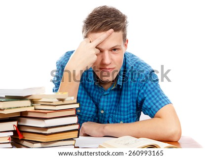 a pissed off teenage student with a pile of books next to him - stock photo