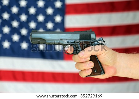 A .45 pistol is held in front of an American Flag. Represents Americas 2nd Amendment, the right to bare arms. Civil Liberty. Personal Protection. Protection of life and property. Gun Control. Guns. - stock photo