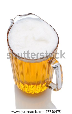 A pitcher of beer shot from a high angle over a white background with reflection. - stock photo