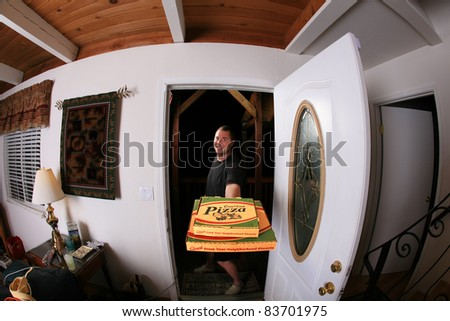 a pizza delivery man brings you Fresh Baked Pizza right to your door shot with a fisheye lens for a fun and funny image. isolated on white with room for your text. in a Generic pizza box - stock photo