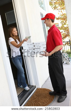 A  pizza delivery man giving order to pretty woman - stock photo