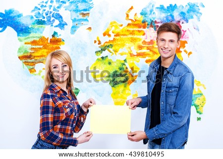 A place for your advertising! Two models hold frame with copyspace in front of wall painted like a map of the world. - stock photo