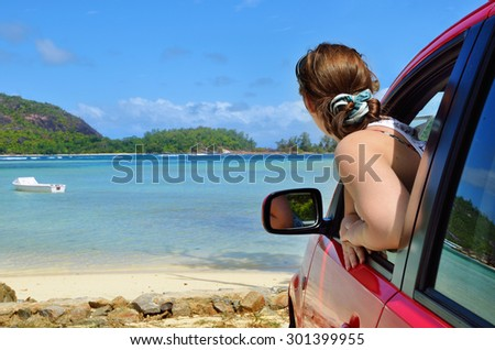 A place of a destination. Young driver woman looking on the sea from opened car's window - stock photo