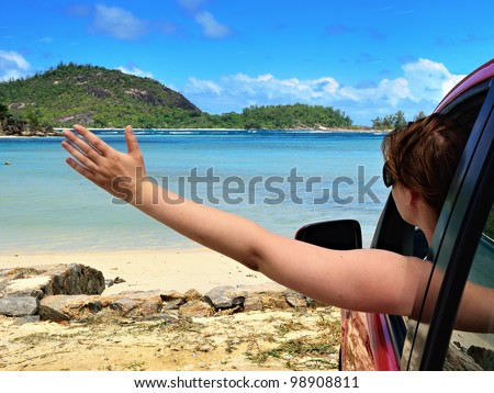 A place of a destination. Young woman makes a happy gesture in the car looking on the sea - stock photo