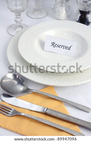 A place setting at a restaurant table with a reserved sign on it.