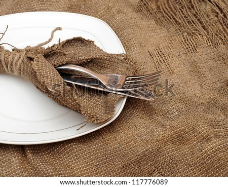A place setting empty plate, silver fork and knife on old sacking texture - stock photo