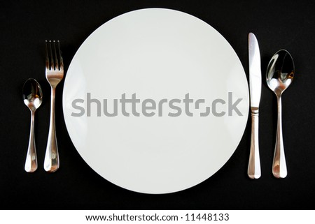 A place setting for dinner against a black background