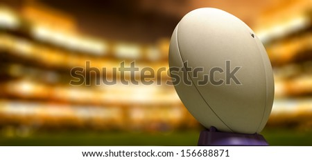 A plain white textured rugby ball on a blue kicking tee in a stadium at night - stock photo