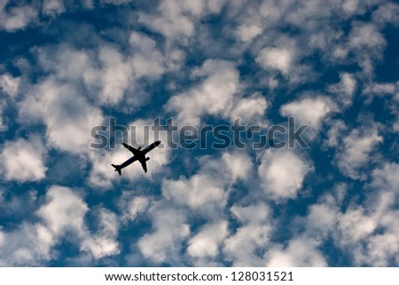 a plane flies overhead in the evening sky - stock photo