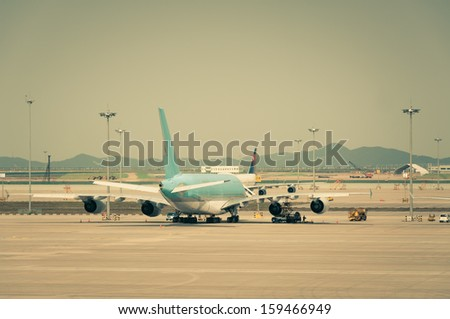 A plane is parked on the tarmac. - stock photo