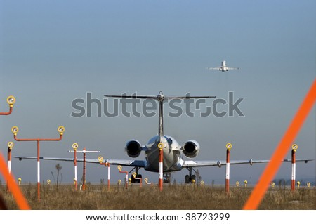 A plane waiting for takeoff while another is already in the air - Concept of jammed air traffic. - stock photo