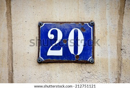 A plaque depicting the number 20 on a rough textured wall. - stock photo